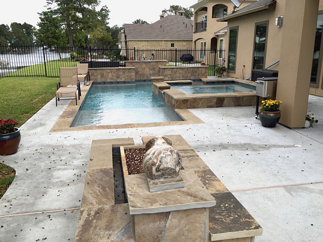 Showcase pool with spa, wall, decking and water feature.