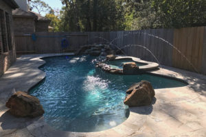 Swimming pool with hot tub and sprinklers.
