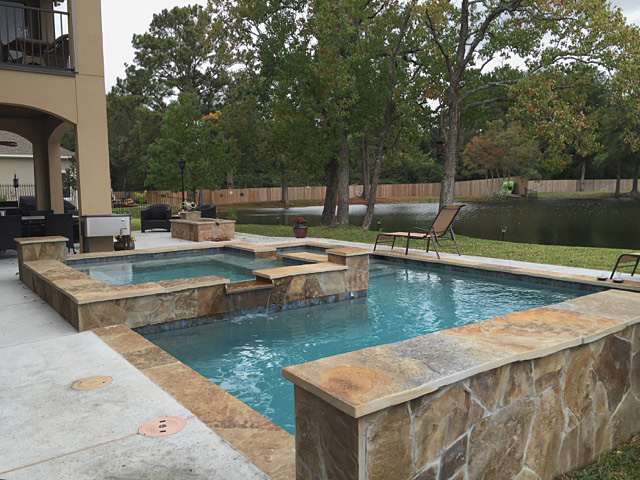 Showcase pool with spa and stone wall.