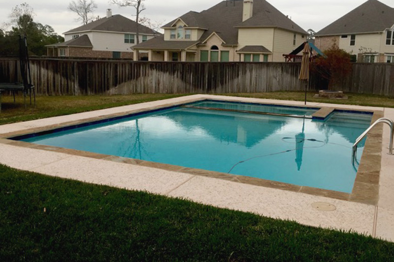 Rectangular pool with a spa and a small deck border.