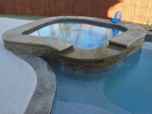 A showcase spa with stone and brick border.
