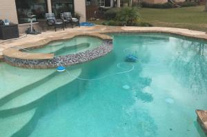 Completed pool in Montgomery, Texas with hot tub and robotic cleaner.