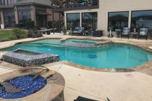 Completed pool in Montgomery, Texas with hot tub, water feature, robotic cleaner and fire pit